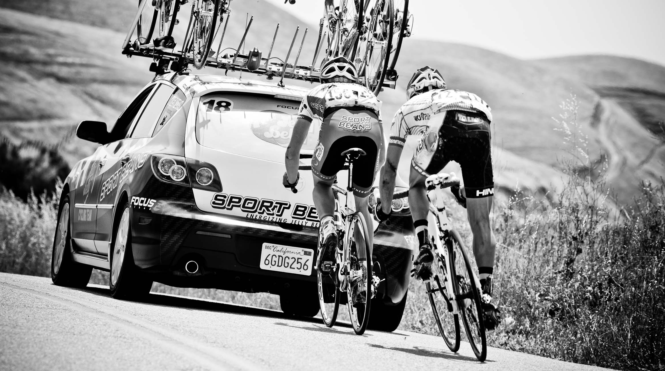 riders tuck behind team car to get back in the race